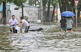 People wade in a flooded street in Ningbo, eastern China's Zhejiang province on July 25, 2021, as Typhoon In-Fa lashes the eastern coast of China. -- Photo: Hector Retamal/ AFP