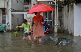A woman and a boy wade in a flooded street in a neighbourhood in Ningbo, eastern China's Zhejiang province on July 25, 2021, as Typhoon In-Fa lashes the eastern coast of China -- Photo: Hector Retamal/ AFP