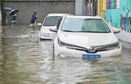 People wade in a flooded street in Ningbo, eastern China's Zhejiang province on July 25, 2021, as Typhoon In-Fa lashes the eastern coast of China -- Photo: Hector Retamal/ AFP