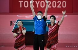 Japan's Jun Mizutani (R) and Mima Ito (L) celebrate after beating China's Xu Xin and Liu Shiwen in their mixed doubles table tennis final match at the Tokyo Metropolitan Gymnasium during the Tokyo 2020 Olympic Games in Tokyo on July 26, 2021 -- Photo : Anne-Christine Poujoulat/ AFP