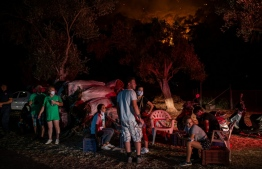 People wait near wildfires in the rural area of Marmaris, district of Mugla, on August 1 2021. - At least three people were reported dead on July 29, 2021 and more than 100 injured as firefighters battled blazes engulfing a Mediterranean resort region on Turkey's southern coast -- Photo: Yasin Akgul/ AFP