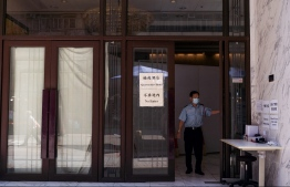 (FILE) A security guard opens the door at a quarantine hotel in North Point, Hong Kong on July 25, 2021 -- Photo: Bertha Wang/ AFP