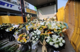 (FILE) Flowers placed as tributes are seen in front of a subway station in memory of flood victims in Zhengzhou, China's central Henan province on July 27, 2021 -- Photo: STR/ AFP