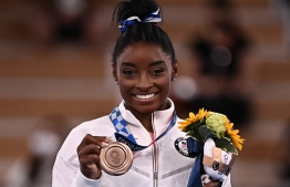 USA's Simone Biles poses with her bronze medal during the podium ceremony of the artistic gymnastics women's balance beam of the Tokyo 2020 Olympic Games at Ariake Gymnastics Centre in Tokyo on August 3, 2021 -- Photo: Lionel Bonaventure/ AFP