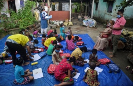 """In this picture taken on July 23, 2021, children of a low-income neighbourhood attend a class at an open-air school 'Vidyachaya' set up by the non-profit Unique Foundation at Porajhar village on the outskirts of Siliguri. - In India where schools have been shut for over a year, one of the longest COVID -19 shutdowns in the world, the fear is that many poor children won't return to education even when schools eventually re-open, creating a """"lost generation"""" of unqualified young people -- Photo: Diptendu Dutta/ AFP"""