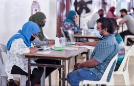 Health workers talking to person about to get inoculated — Photo: Nishan Ali/ Mihaaru