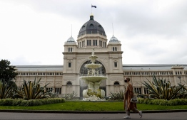 A woman walks along Carlton Gardens in downtown Melbourne on August 5, 2021, as authorities there announced a sixth lockdown for the city in efforts to bring the Delta outbreak to heel -- Photo: Con Chronis/ AFP