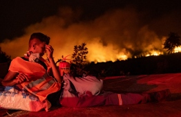 TOPSHOT - A volunteer rests as flames rise from a forest burning in the background near Akcayaka, a town in the Mugla province, on August 6, 2021. - In Turkey, at least eight people have been killed and dozens more hospitalised as the country struggles against its deadliest wildfires in decades. (Photo by Yasin AKGUL / AFP)