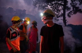 Volunteers stand near smoke rising in the village of Akcayaka in the Milas area of the Mugla province, on August 6, 2021. - In Turkey, at least eight people have been killed and dozens more hospitalised as the country struggles against its deadliest wildfires in decades. (Photo by Yasin AKGUL / AFP)