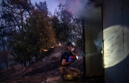 A firefighter uses a flashlight in the village of Akcayaka in Milas area of the Mugla province, on August 6, 2021. - In Turkey, at least eight people have been killed and dozens more hospitalised as the country struggles against its deadliest wildfires in decades. (Photo by Yasin AKGUL / AFP)