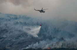 A helicopter drops water on a wildfire on an area near the village of Ikizce, in the Mugla province, on August 6, 2021. - In Turkey, at least eight people have been killed and dozens more hospitalised as the country struggles against its deadliest wildfires in decades. (Photo by Yasin AKGUL / AFP)