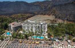 This aerial picture taken on August 7, 2021, shows the Quadas Hotel (R) with a ravaged area and burnt trees in the background in Icmeler along the coast of the Mugla district as Turkey struggles against its deadliest wildfires in decades. - Greece and Turkey have been fighting devastating fires for more than a week as the region suffers its worst heatwave in decades. Officials and experts have linked such intense weather events to climate change. (Photo by Yasin AKGUL / AFP)