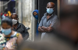 Residents watch army health officials (not pictured) conducting the Covid-19 coronavirus mobile vaccination drive in a locality in Colombo on August 12, 2021. (Photo by Ishara S. KODIKARA / AFP)