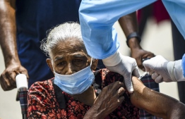 A Police health official inoculates a woman with a dose of the Sinopharm vaccine against the Covid-19 coronavirus at a vaccination camp held in Colombo on August 14, 2021. (Photo by ISHARA S.  KODIKARA / AFP)