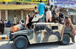 Taliban fighters and local residents sit on an Afghan National Army (ANA) Humvee vehicle along the roadside in Laghman province on August 15, 2021 -- Photo: AFP