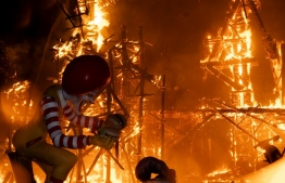 Ninots (cardboard figurines) burn as one installation of the Fallas Festival is put on fire in Valencia on September 5, 2021. - The Fallas, the major festival in the Valencia region featuring parades of floats and giant cardboard sculptures, was cancelled in 2020 and was postponed this year from March to September, due to the pandemic. Its last cancellation was in 1939 due to the Spanish Civil War. (Photo by JOSE JORDAN / AFP)