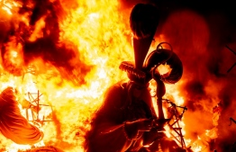 A ninot (cardboard figurine) burns as an installation of the Fallas festival is put on fire during the last night of the festival in Valencia on September 5, 2021. - The Fallas, the major festival in the Valencia region featuring parades of floats and giant cardboard sculptures, was cancelled in 2020 and was postponed this year from March to September, due to the pandemic. Its last cancellation was in 1939 due to the Spanish Civil War. (Photo by JOSE JORDAN / AFP)