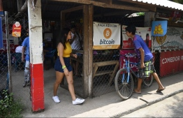 People are seen in a store where bitcoins are accepted in El Zonte, La Libertad, El Salvador on September 4, 2021. - The Congress of El Salvador approved in June a law that will make bitcoin legal tender in the country from September 7, with the aim of boosting its economy although analysts warn of a negative impact. -- Photo: Marvin Recinos/ AFP