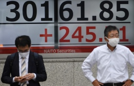 Pedestrians stand in front of a stock indicator displaying numbers of the 225-issue Nikkei Stock Average climbed 245.71 points in Tokyo on September 8, 2021. -- Photo: Kazuhiro Nogi/ AFP