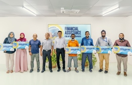 Managing Director of Ensis Abdul Waheed Thowfeeq (right, five) stands with Ensis employees that received financial assistance from Ensis Fisheries -- Photo: Ensis Fisheries