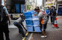 Workers (C) load boxes onto a truck after police officers from the National Security Department take away items from the June 4 museum dedicated to the 1989 Tiananmen Square crackdown, in Hong Kong on September 9, 2021. -- Photo: Isaac Lawrence/ AFP