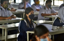 Students attend their class at the Rajuk Uttara Model College in Dhaka on September 12, 2021, as Bangladesh schools reopened after 18 months in one of the world's longest shutdowns due to the Covid-19 coronavirus pandemic. (Photo by Munir Uz zaman / AFP)