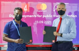 CEO of MTCC Adam Azim (L) and Managing Director of BML Tim Sawyer shows the MoU they signed to introduce a digital payment system for the public transport provided by MTCC -- Photo:  BML
