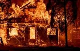 (FILES) In this file photo taken on July 24, 2021 a home burns as flames from the Dixie fire tear through the Indian Falls neighborhood of unincorporated Plumas County, California. - California is on fire, literally and figuratively. The wildfires that are charring the state's forests are burning so voraciously that they're part of the recall vote that will decide the fate of the governor. Photo: Josh Edelson/ AFP