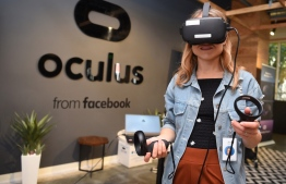 (FILES) In this file photo taken on October 23, 2019, Facebook employee Elza Uzmanoff tries out an Oculus device at the company's corporate headquarters campus in Menlo Park, California. - Virtual reality meetings, $7,000 all-in-one kits and digital hot desking: Big Tech is rolling out premium tools as the work-from-home era looks set to last well beyond the pandemic.