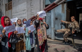 A Taliban fighter watches as Afghan women hold placards during a demonstration demanding better rights for women in front of the former Ministry of Women Affairs in Kabul on September 19, 2021. -- Photo: Bulent Kilic/ AFP