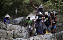 Haitian migrants cross the jungle of the Darien Gap, near Acandi, Choco department, Colombia, heading to Panama, on September 26, 2021, on their way trying to reach the US. - From Acandi, they started on foot -- and armed with machetes, lanterns and tents -- the dangerous trek of at least five days to Panama through the Darien jungle, battling snakes, steep ravines, swollen rivers, tropical downpours and criminals often linked to drug trafficking. -- Photo: Raul Arboleda/ AFP