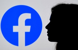 (FILES) In this file photo illustration, a person looks at a smart phone with a Facebook App logo displayed on the background, on August 17, 2021, in Arlington, Virginia -- Photo by Olivier Douliery / AFP