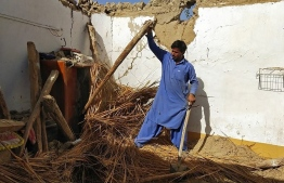 A resident removes debris of his mud house that collapsed following an earthquake in the remote mountainous district of Harnai on October 7, 2021, as around 20 people were killed and more than 200 injured when a shallow earthquake hit southwestern Pakistan in the early hours of October 7.  -- Photo:  Banaras Khan / AFP