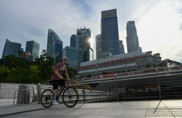 A man cycles past the city skyline in Singapore on October 13, 2021. -- Photo: Roslan Rahman / AFP